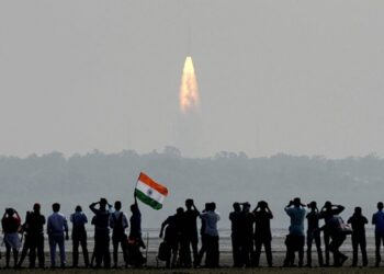 Pessoas assistem de longe ao lançamento do foguete PSLV-C37 na Organização de Pesquisa Espacial Indiana (ISRO) em Sriharikota. O foguete conseguiu levar ao espaço e colocar em órbita um número recorde de 104 satélites individuais, feito inédito celebrado pela agência indiana (Foto: Arun Sankar/AFP)