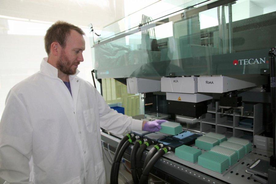 Brian Thompson, um associado de pesquisa no Single Cell Genomics Center no Bigelow Laboratory for Ocean Sciences, carrega amostras em um robô de manipulação de líquidos. O Laboratório recentemente publicou os detalhes de avanços significativos na tecnologia de genômica de célula única, que permite aos cientistas estudar os genes de células individuais.