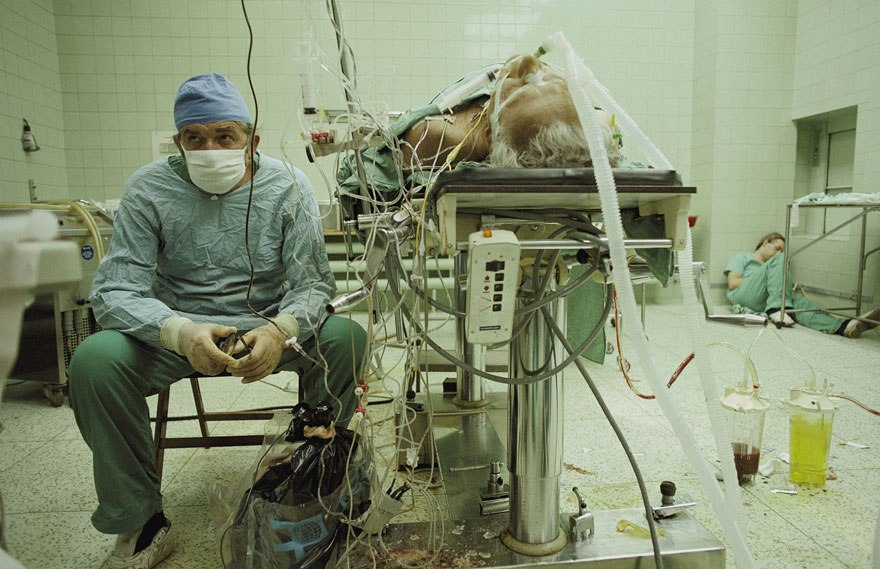 O cirurgião Zbigniew Religa após um transplante cardíaco de 23 horas, observando os sinais vitais do paciente. Imagem: National Geographic.