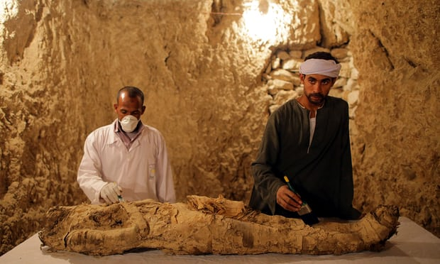 Arqueólogos egípcios com uma múmia recentemente descoberta em Luxor. Fotografia: Khaled Elfiqi / EPA