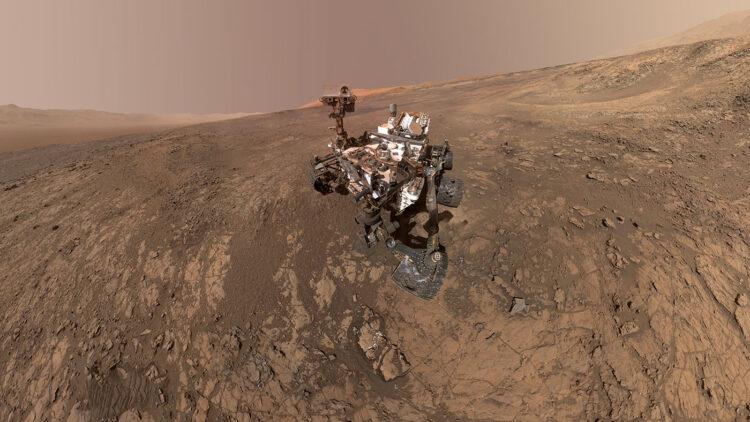 """Este auto-retrato do Criosity Mars da NASA mostra o veículo em Vera Rubin Ridge, que vem sendo investigado nos últimos meses. Diretamente atrás do rover está o começo de uma encosta rica em argila que os cientistas estavam ansiosos para começar a explorar. Na próxima semana, o Curiosity começou a subir essa encosta. À esquerda está o norte e o oeste está à direita, com a borda da """"Gale Crater"""" no horizonte de ambas as bordas. Fonte: NASA/JPL-Caltech/MSSS."""