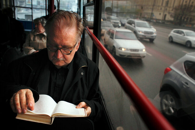 A passenger reads a book sitting on a bus, in Moscow, Russia, Thursday, April 22, 2010. (AP Photo/Alexander Zemlianichenko)