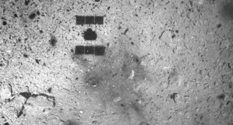 A espaçonave japonesa Hayabusa 2 (cuja sombra é visível no topo da imagem) tirou esta foto do asteroide Ryugu em 22 de fevereiro, cerca de um minuto depois de tocar em sua superfície e depois levantar novamente.