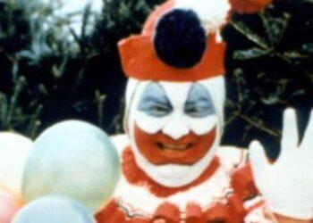 O serial killer americano John Wayne Gacy vestido como um palhaço.