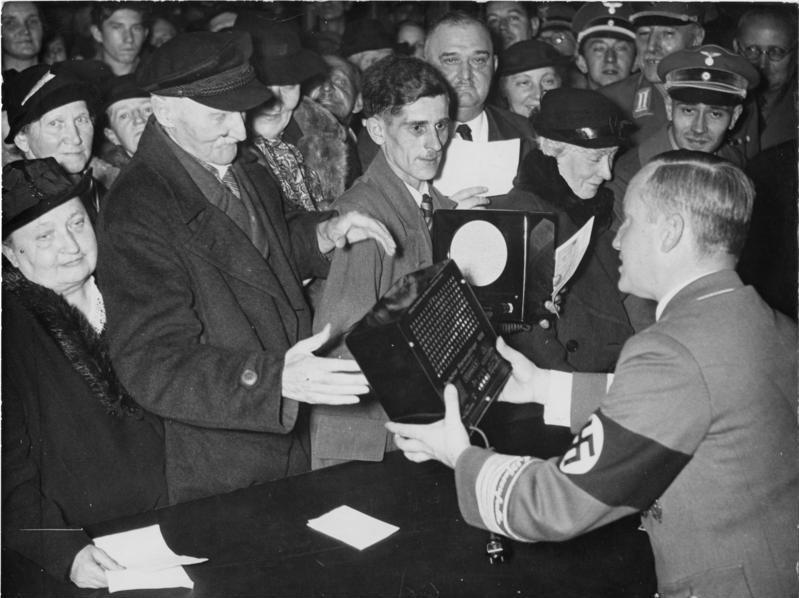 Distribuição gratuita de rádios em Berlim no dia de aniversário de Goebbels em 1938. Por Bundesarchiv, Bild 183-H14243 / Nau / CC-BY-SA 3.0, CC BY-SA 3.0