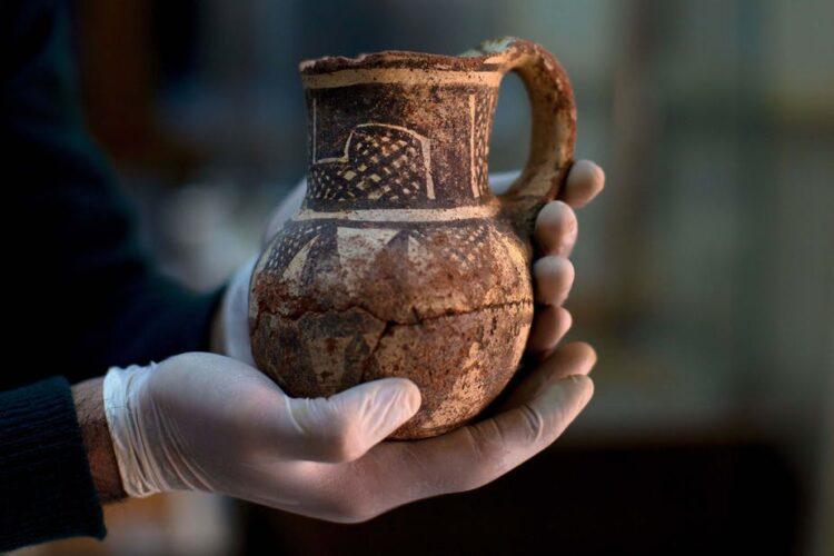 Um arqueólogo sírio detém um artefato que foi transportado para Damasco para proteção durante a Guerra Civil Síria. (Foto AP / Hassan Ammar)