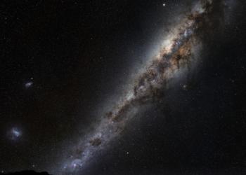 Assim se parece a Via Láctea a partir da Terra. Aquelas duas manchas brilhantes à esquerda são as Núvens de Magalhães, duas galáxias anãs que orbitam a Via Láctea. (ESO/S. Brunier).