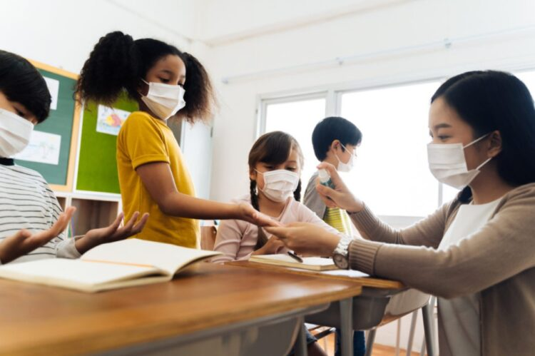 Na imagem acima, professora usa spray de álcool para desinfetar as mãos dos alunos em sala de aula. (IStock)