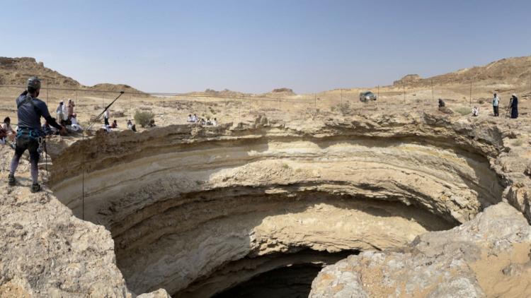 Cientistas ao redor do buraco para o poço do inferno